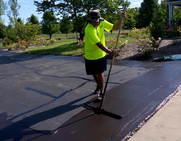 Guy sealing asphalt driveway 2